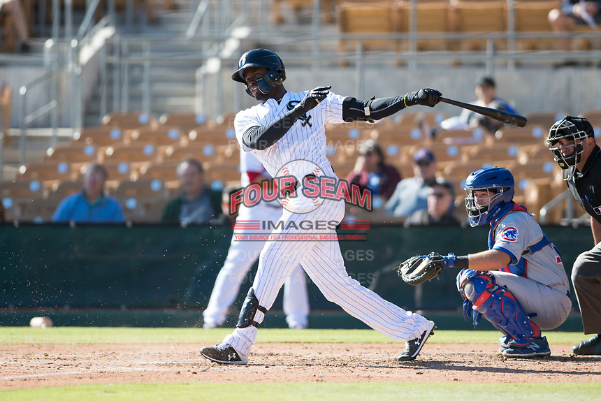 Glendale Desert Dogs center fielder Luis Robert (20), of the Chicago White Sox organization, follows through on his swing in front of catcher P.J. Higgins (12) and home plate umpire Jeremy Riggs during an Arizona Fall League game against the Mesa Solar Sox at Camelback Ranch on November 12, 2018 in Glendale, Arizona. Glendale defeated Mesa 4-2. (Zachary Lucy/Four Seam Images)