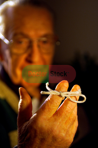 elderly man sitting at home with string tied on index finger as reminder