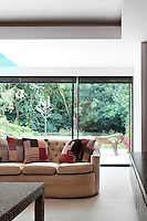 A living room with a slding glass door, which leads out to the garden. A group of red pattern cushions are placed on a leather sofa, which is upholstered in a neutral fabric.