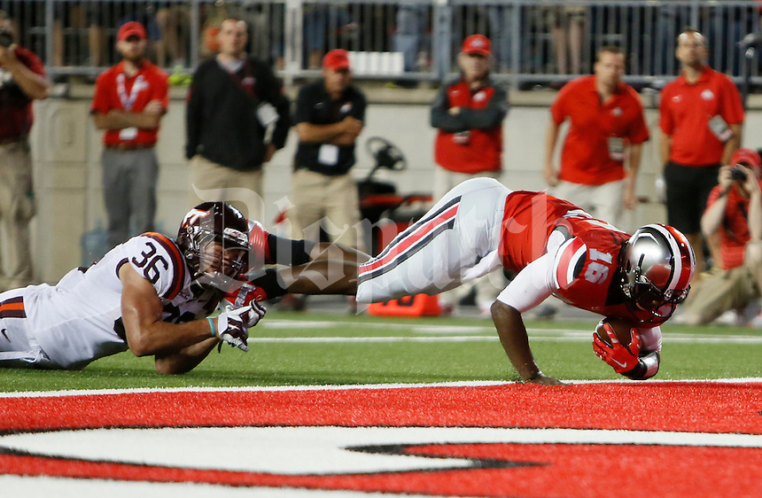 Ohio State Buckeyes quarterback J.T. Barrett (16) scores a touchdown against Virginia Tech Hokies linebacker Chase Williams (36) in the first quarter at OhioStadium September 6, 2014. (Dispatch photo by Eric Albrecht)
