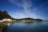 Looking past the famous Mangonui Fish shop built over the water & anchored boats to Cole Pt and the entrance to Mangonui Harbour.