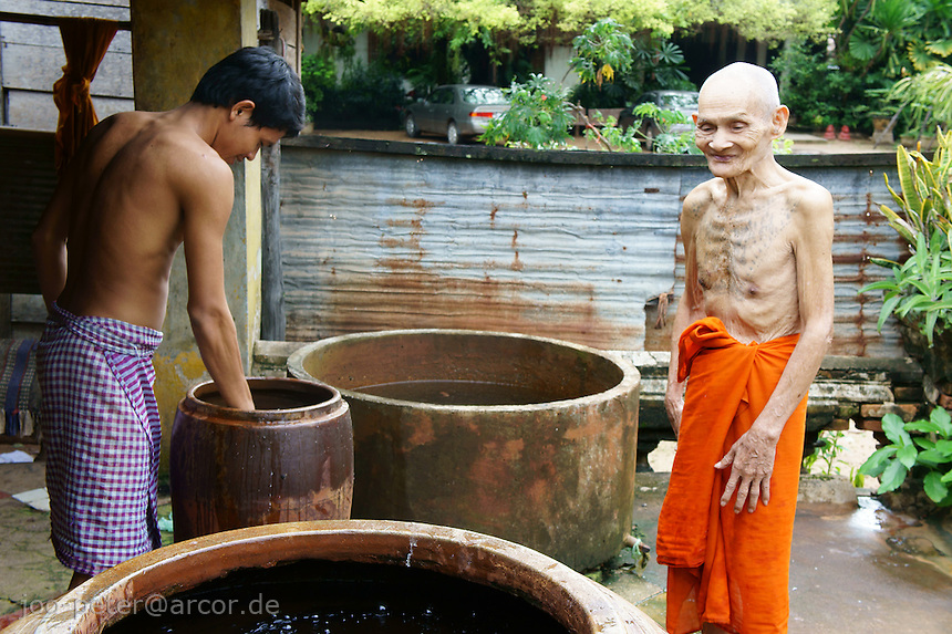 young and old monk taking bath in monastery, Siem Reap,  Cambodia, August 2011