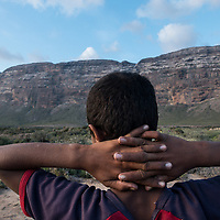 Dec. 25, 2014 - Socotra, Yemen. A young boy looks out to the mountains in Neet.  The island's plant life is under threat from human encroachment, and non-native animals and plants. © Nicolas Axelrod / Ruom