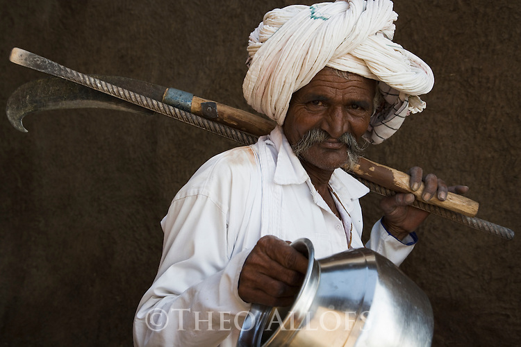 Old Gujarat man carrying tools and water jug, Gujarat, India --- Model Released