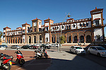 White taxi cars outside historic railway station building, Jerez de la Frontera, Spain
