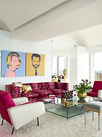 The luxurious penthouse apartment is full of edgy chic and sizzling colour. In the living room a pair of silk-screened prints by Andy Warhol hang above a 1960s Edward Wormley sofa upholstered in a Scalamandré velvet. The Louis XVI stools, circa 1780, are from Bernd Goeckler Antiques. A pair of circa-1958 two-toned armchairs by Pierre Guariche flank a cocktail table by Fredrikson Stallard.