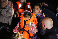 Pictured: A young girl is helped to safety by her father as they both land in Lesvos Wednesday 09 March 2016<br /> Re: Migrants have been landing on beaches near the area of the airport at the area of Mytilene in Lesvos island, Greece
