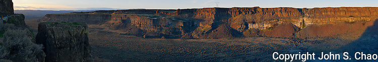 Panorama of sunset highlighting ancient volcanic basalt walls and waterfall in Frenchman Coulee. One site in the Ice Age Floods National Geologic Trail. Historic Vantage Highway is on left side of frame. Washington State.