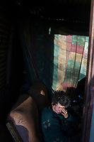 KRUGERSDORP, SOUTH AFRICA - JULY 18: An Afrikaner woman sits inside her shack in Munsieville township on July 18, 2018 in Krugersdorp a suburb in Johannesburg, South Africa. This black township, where South Africans and African immigrants live, now also has a separate section of poor white Afrikaners. They live side my side but they don't mix unless they have too. Many of the residents survive by begging at traffic lights and doing odd jobs. (Photo by Per-Anders Pettersson/Getty Images)