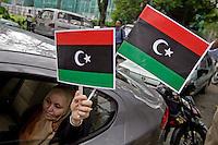 SHS10 KUALA LUMPUR (MALASIA) 25/2/2011.- Una mujer sostiene dos banderas de Libia durante una protesta para exigir la caída del líder libio, Muamar al Gadafi, en el poder desde 1969, cerca de la embajada de Libia en Kuala Lumpur, Malasia, hoy, viernes 25 de febrero de 2011. EFE/SHAMSHAHRIN SHAMSUDIN..
