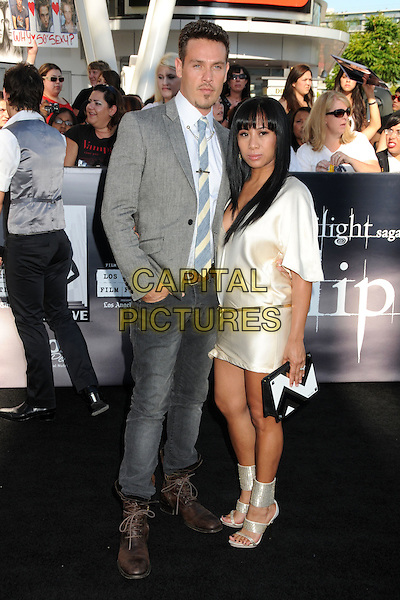 "KEVIN ALEJANDRO & GUEST .""The Twilight Saga: Eclipse"" Los Angeles Premiere at the 2010 Los Angeles Film Festival held at Nokia Theatre LA Live, Los Angeles, California, USA, 24th June 2010..full length suit jacket jeans tie gold cream silk satin dress  grey gray .CAP/ADM/BP.©Byron Purvis/AdMedia/Capital Pictures."