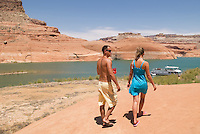 Young couple walking near shore of Lake Powell, Utah