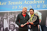 Tennis legend Boris Becker (left) gives the racket he won Wimbledon tournament in 1985 with to Mission Hills Vice Chairman Tenniel Chu during the press conference for the opening of Boris Becker Tennis Academy at Mission Hills Resort on 19 March 2016, in Shenzhen, China. Photo by Lucas Schifres / Power Sport Images
