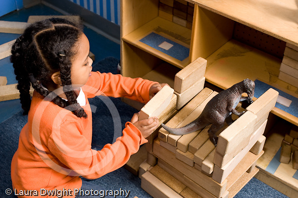 Educaton preschool 4-5 year olds block area girl working on construction made of wooden blocks plastic dinosaur inside horizontal