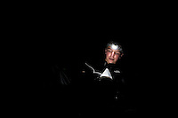 Photo story of Philmont Scout Ranch in Cimarron, New Mexico, taken during a Boy Scout Troop backpack trip in the summer of 2013. Photo is part of a comprehensive picture package which shows in-depth photography of a BSA Ventures crew on a trek.  In this photo a headlamp lights up a BSA Venture Crew member's book as he reads ghost stories out load to the rest of his crew.  <br /> <br /> The  Photo by travel photograph: PatrickschneiderPhoto.com