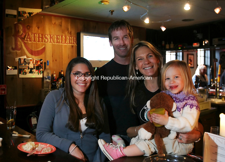SOUTHBURY, CT; 22 OCTOBER 2006; 102206BZ03-  From left- Hayley Holbrook, 16, Chris Antilla, owner, Janet Antilla, owner, and Parker Antilla, 2, pose in the Rathskeller Lounge and Cafe in Southbury Sunday afternoon.  The Antilla family held a free pig roast to celebrate the restaurant's second anniversary and to collect contributions for the Southbury Needy Fund.  They hoped to raise $500 at the event.<br /> Jamison C. Bazinet Republican-American