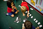 Aysia Alford, 6, counts as classmates Ethan Kushing (top), 6, and Levi Ruus, 6, play dominoes in their kindergarten class at Kennesaw Charter School in Kennesaw, Georgia, April 1, 2010. The 440-student school, which used to be managed by Imagine Schools, is now self-managed.