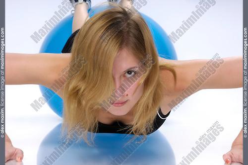 Young woman doing push-ups on exercising ball