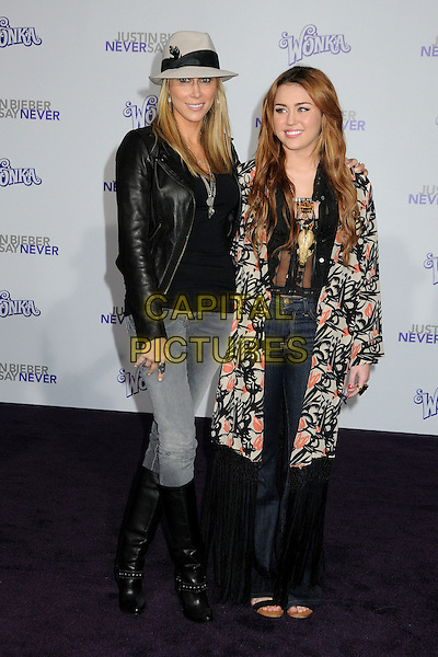 "LETICIA ""TISH"" CYRUS & MILEY CYRUS .""Justin Bieber: Never Say Never"" Los Angeles Premiere held at Nokia Theater L.A. Live, Los Angeles, California, USA, .8th February 2011..full length mother family mom mum family hat black leather jacket tassels fringe bed jacket kimono jeans knee high boots wide leg flares grey gray denim print orange fedora feather  .CAP/ADM/BP.©Byron Purvis/AdMedia/Capital Pictures."