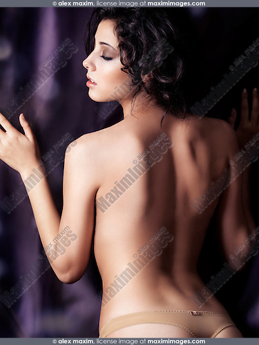 Young sexy woman standing topless against dark curtain with her back towards the camera