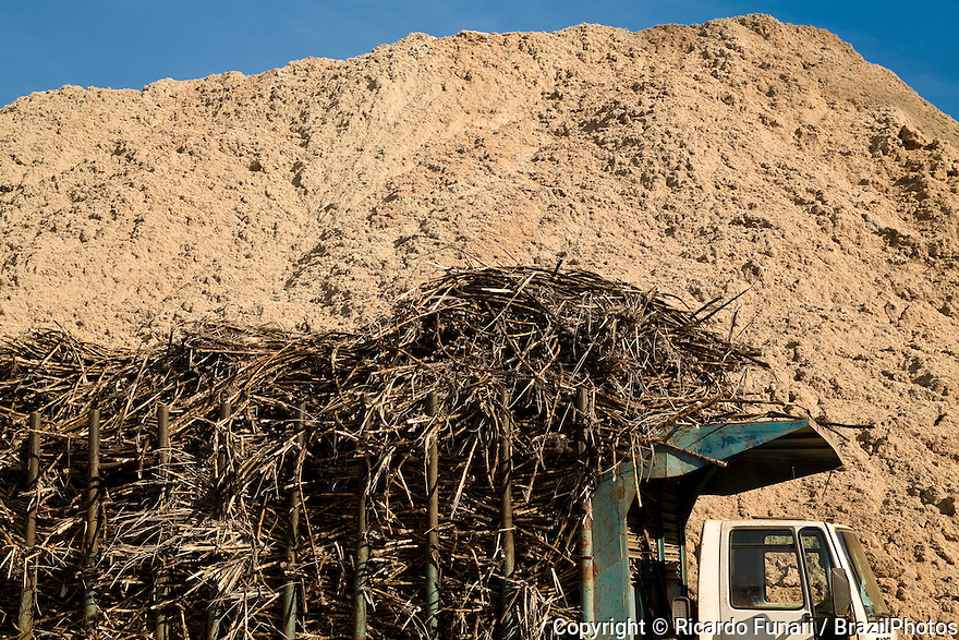 Truck loaded with sugarcane wait in line for unloading at Ester ethanol and sugar Plant in front of pile of sugarcane bagasse, used for generating energy, Cosmopolis city, Sao Paulo state, Brazil.