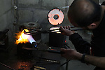 A Palestinian jeweller melts gold at his workshop in Gaza city on February 18, 2013. Photo by Ashraf Amra