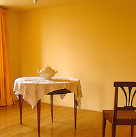 A porcelain tureen stands on a small round dining table in this sparsely furnished yellow room