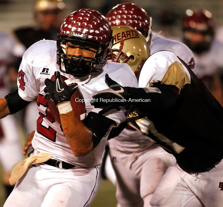 Waterbury, CT- 04, November 2010-110410CM07 Torrington's Brenden Lytton carries the ball as Sacred Heart's Adam Pitts comes from behind for the tackle Thursday night at Municipal Stadium in Waterbury.  Sacred Heart defeated Torrington 42-27. Christopher Massa Republican-American