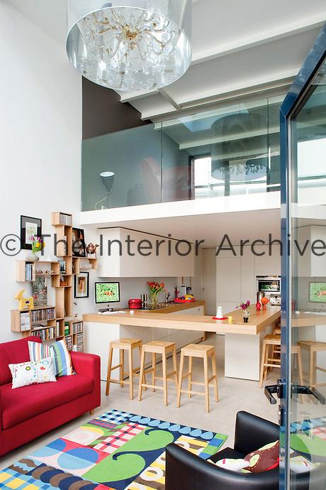 This kitchen living area features an oak breakfast bar, a corner of which beside a wall-mounted modular bookshelf doubles as an office