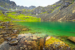 Emerald green colors of Lower Reed Lake surrounded by Talkeetna Mountains. Hatcher Pass, Mat-Su Valley, Southcentral Alaska, Summer.