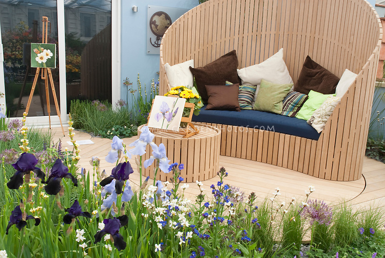 Painting in the garden, with easel, watercolor, irises, bench seat and table furniture next to house sliding doors, in blue tones for pretty deck landscaping