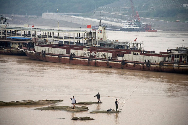 Men fish in the Yangtze River as barges pass by Chongqing, China.
