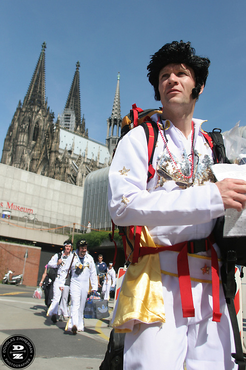 """With the Kölner Dom cathedral in the background USA National Soccer Team fan Pat Ryan of Kansas City, MO, leads a tour group of fans dressed up in flight suits as the American Icon Elvis from the Cologne, Germany train station.  The group was traveling by train to Cologne, Germany from Düsseldorf Airport and their hotel. They arrived at Düsseldorf Airport in Germany on Saturday morning, June 10th, 2006 after an overnight flight from JFK airport in New York City.  The fans were part of a tour group, called """"2006 World Cup Trip"""" arraigned by Pat Ryan from Kansas City, MO by his travel company """"Ryan Adventures. They were among the thousands of American fans who have descended on Germany to support the USA National team during the 2006 FIFA World Cup. The first game for the USA is against the Czech Republic in Gelsenkirchen on Monday June 12th...For a website of the tourgroup:..http://www.2006worldcuptrip.com/..Pat Ryan can also be reached by cell phone with any questions 1.913.963.7168"""