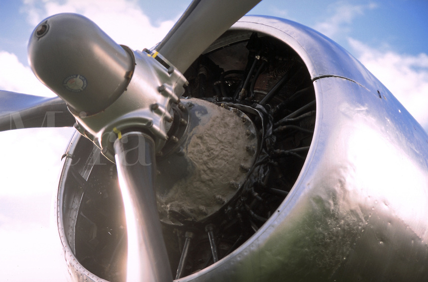Close up view of a steel aircraft engine and propeller.
