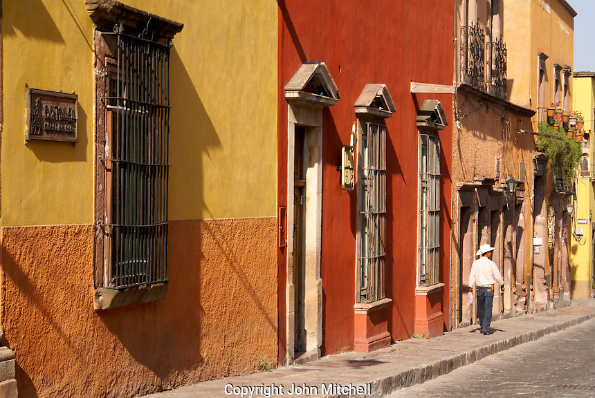 Mexican man walking past Spanish colonial houses on Canal Street in San Miguel de Allende, Mexico