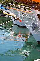 The bow of several yachts boats ships, white, wood, with reflections in the water, moored at the dock. Luka Gruz harbour. Dubrovnik, new city. Dalmatian Coast, Croatia, Europe.