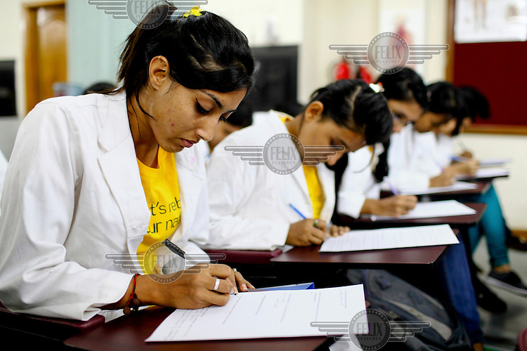 Students complete a paper during a class at the Asian University for Women. /Felix Features