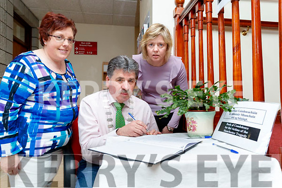 Mayor Michael O'Shea signs a book of condolences Ellen O'Keeffe and Gene Foley at Kerry County Council on Wednesday.