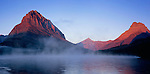 Grinnell Point and Mount Wilbur are lit by sunrise on a misty Swiftcurrent Lake in Glacier National Park, Montana.