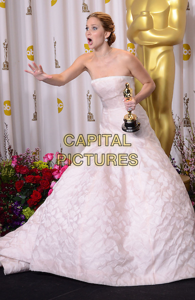 Jennifer Lawrence (wearing Dior Haute Couture).85th Annual Academy Awards held at the Dolby Theatre at Hollywood & Highland Center, Hollywood, California, USA..February 24th, 2013.pressroom oscars full length white pale pink strapless dress gown voluminous award trophy winner hand arm mouth open funny profile .CAP/ADM/RE.©Russ Elliot/AdMedia/Capital Pictures.