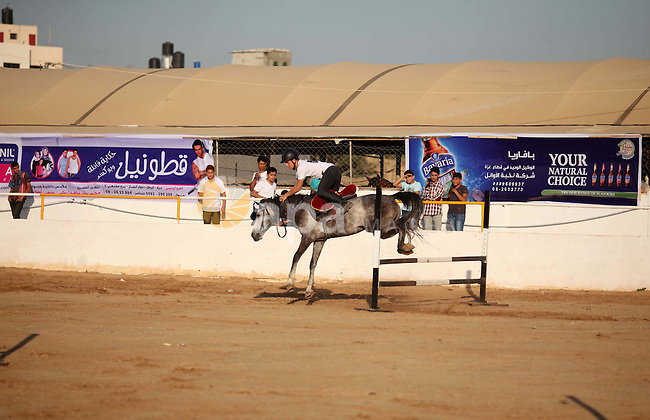 A Palestinian rider clears a jump with his horse during a jumping competition in Gaza city on June 12, 2015. The competition organized by Gaza equestrian club participant by 35 rider from the besieged coastal enclave. Photo by Ashraf Amra