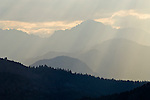 Crepuscular rays puncture the clouds and mountains in the mist on the east side of the Sierra Nevada Range, California