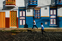 Colombian school kids run in front of a brightly painted colonial house in Jericó, a village in the coffee region (Zona cafetera) of Colombia, 24 April 2018.