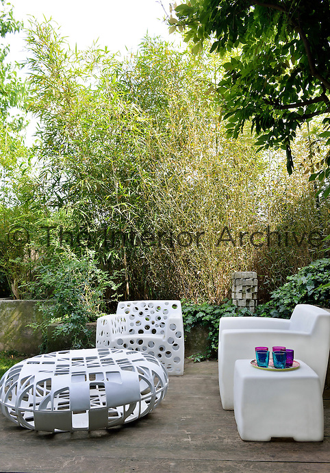 Contemporary white furniture is arrranged on a garden terrace