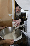 Israel, Bnei Brak. Passover at the Premishlan congregation, the Motzot baking on Passover eve, the Rabbi is pouring the freshly ground flour, 2005<br />