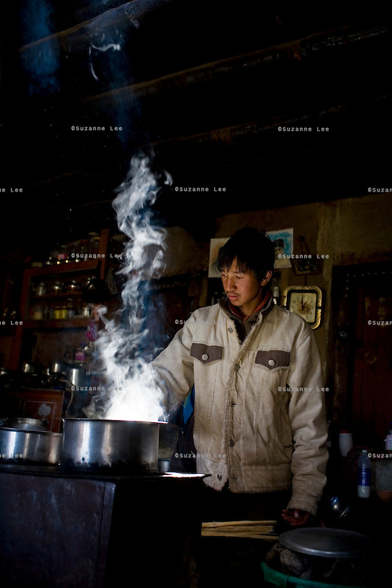 Rinchen Namgyal, aged 19, helps his mother with the cooking on 2nd June 2009. They run a home stay program in Ulley Valley, a scattered village of only 5 houses, one school, 38 people, 4 school children, and 4 pet dogs. The village is not accessible by road. The homestay program is managed by 'Snow Leopard Conservation Organisation', an NGO that helps families in the mountains that face constant snow leopard attacks on their livestock. Leh town is 3505m above sea level, in the Indian Himalayan mountains, in the valley of Ladakh is located in the Indian Himalayas, in the northern state of Jammu and Kashmir. Photo by Suzanne Lee