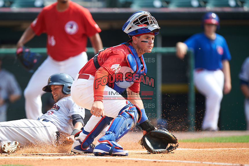 Buffalo Bisons catcher Sean Ochinko (9) waits for a throw as Mason Williams (9) slides home safely during a game against the Scranton/Wilkes-Barre RailRiders on June 10, 2015 at Coca-Cola Field in Buffalo, New York.  Scranton/Wilkes-Barre defeated Buffalo 7-2.  (Mike Janes/Four Seam Images)