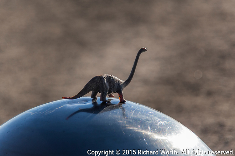 A toy dinosaur sits atop a large decorative metal ball at the par course at the San Leandro Marina Park.