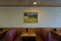 Empty booth with table settings with bucolic European landscape poster in wall in restaurant diner.