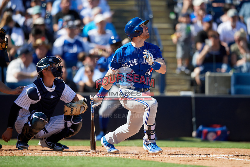 Toronto Blue Jays first baseman Billy McKinney (28) follows through on a swing in front of catcher Kyle Higashioka (66) during a Grapefruit League Spring Training game against the New York Yankees on February 25, 2019 at George M. Steinbrenner Field in Tampa, Florida.  Yankees defeated the Blue Jays 3-0.  (Mike Janes/Four Seam Images)